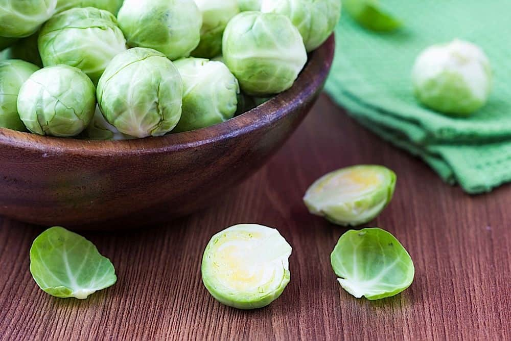 Brussels sprouts in a wooden bowl on the table, tasty, healthy vegetable bio products