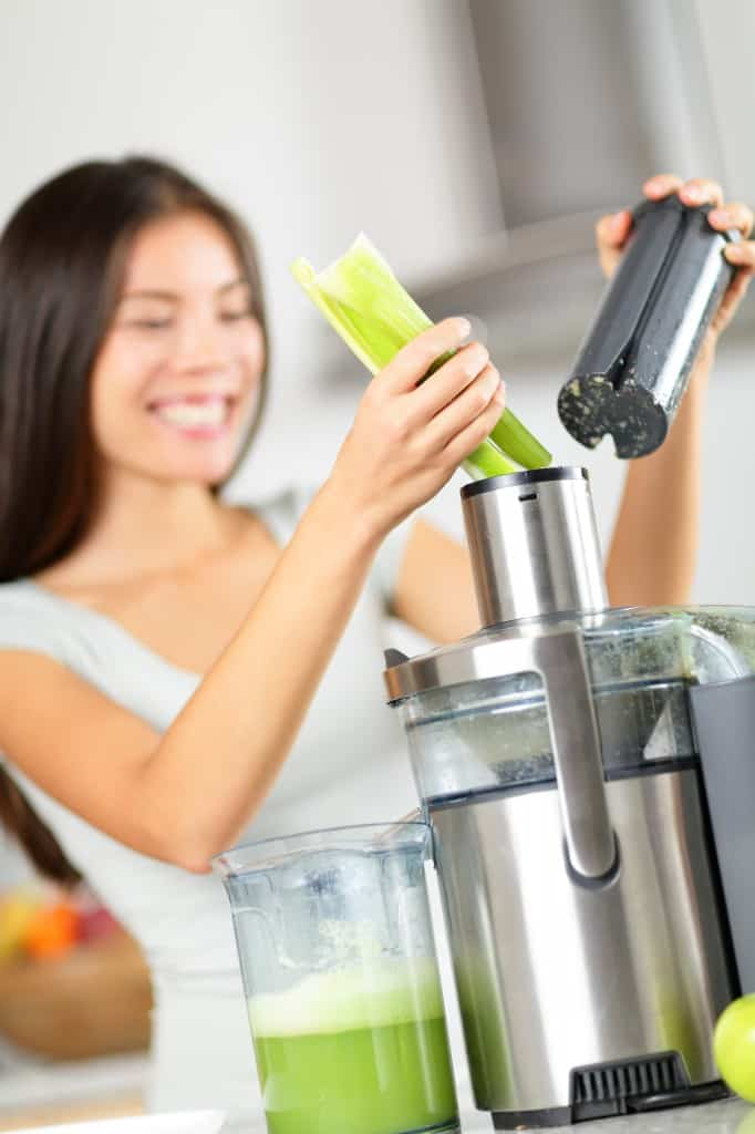 Vegetable juice - woman juicing green vegetables